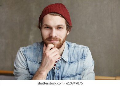 Enjoying nice day. Portrait of cheerful attractive bearded hipster in good mood having rest indoors, sitting against grey concrete wall background at modern cafe, feeling relaxed and carefree