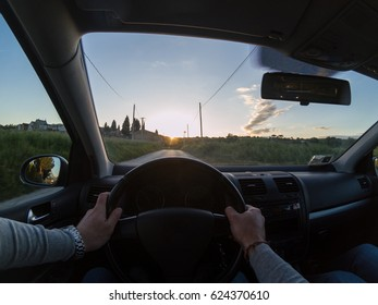 Enjoying a nice road trip at sunset. Young adult man driving a car. Personal perspective.