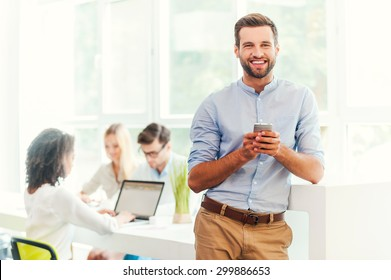 Enjoying office life. Joyful young man holding mobile phone and looking at camera while his colleagues working in the background