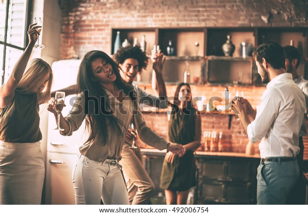 Enjoying party with best friends. Cheerful young people dancing and drinking while enjoying home party on the kitchen