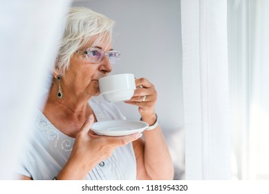 Enjoying a perfect afternoon at home. Age, drink and people concept - happy smiling senior woman with cup of tea or coffee at home. Portrait of a active senior woman with cup