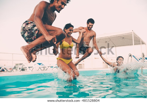 Enjoying pool party with friends. Group of beautiful young people looking happy while jumping into the swimming pool together