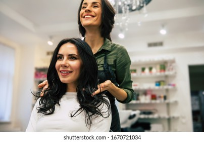 Enjoying the procedure. Close up photo of a happy woman in white sweater looking in the mirror and smiling while getting her hair done in a salon.