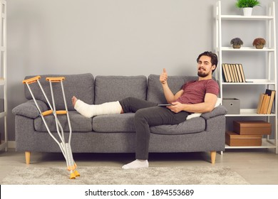 Enjoying recovery sickness benefit after injury in domestic accident. Positive young man with broken leg in plaster cast sitting on sofa at home, using tablet, looking at camera and giving thumbs-up