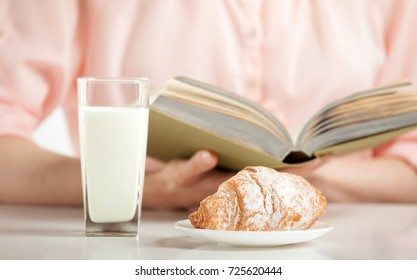Enjoying relaxing moment with a book, croissant and glass of milk; unrecognizable young woman having croissant and milk for lunch while reading a book