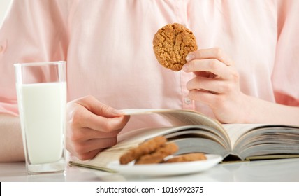 Enjoying relaxing moment with a book, oat cookies and a glass of milk; unrecognizable young woman having oat cookies and milk for lunch while reading a book