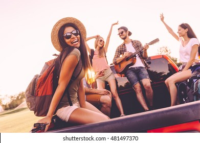 Enjoying road trip with best friends. Group of young cheerful people dancing and playing guitar while enjoying their road trip in pick-up truck together
