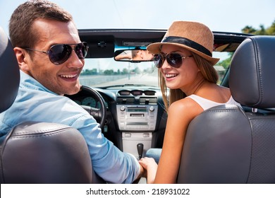 Enjoying road trip together. Beautiful young couple enjoying road trip in their convertible and looking over shoulder with smile