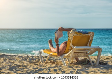 Enjoying the sea and sun. Funny looking man tanning on the beach.