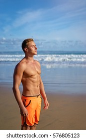 Enjoying the sea and sun. Handsome and strong young man tanning on the beach.