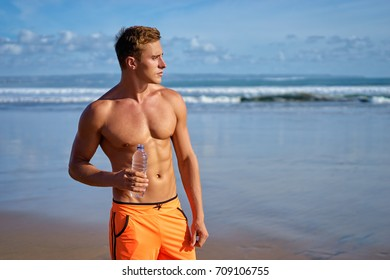 Enjoying the sea and sun. Handsome strong young man drinking water on the beach.