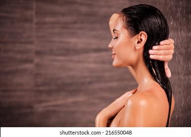 Enjoying a shower. Side view of beautiful young shirtless woman taking shower