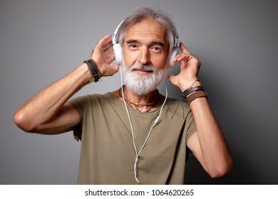 Enjoying the sound of music. Studio portrait of handsome senior man with gray beard and headphones.