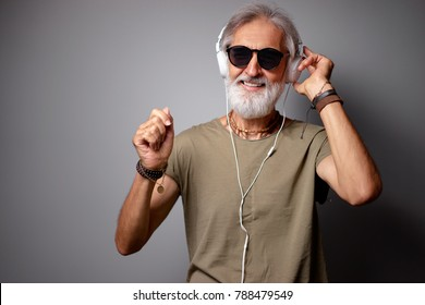 Enjoying the sound of music. Studio portrait of handsome senior man with gray beard and headphones.