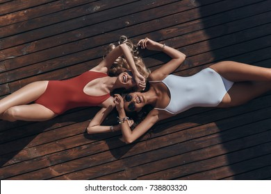 Enjoying summer. Top view of two attractive young women in swimwear smiling while lying down outdoors