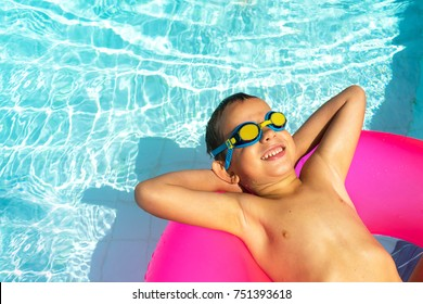 enjoying sun vacation concept top view of funny boy in blue yellow swim glasses  on the pink air tube
