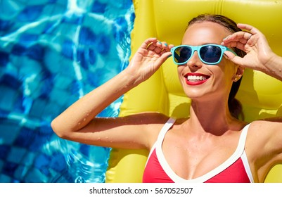 Enjoying suntan and vacation. Colorful portrait of pretty young woman in red swimsuit lying on yellow inflatable mattress at swimming pool.