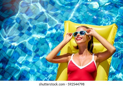 Enjoying suntan and vacation. Colorful portrait of pretty young woman in red swimsuit lying on yellow inflatable mattres at swimming pool.
