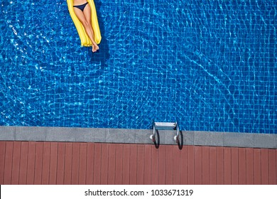 Enjoying suntan. Vacation concept. Top view of slim young woman on the yellow air mattress in the big swimming pool.