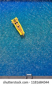 Enjoying suntan. Vacation concept. Top view of slim young woman in bikini on the yellow air mattress in the big swimming pool.