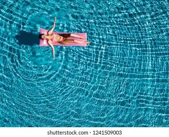 Enjoying suntan. Vacation concept. Top view of slim young woman in bikini on the pink air mattress in the big swimming pool.