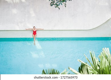 Enjoying suntan. Vacation concept. Top view of slim young woman in red swimsuit in the swimming pool.