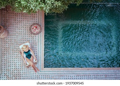 Enjoying suntan. Vacation concept. Top view of young woman on the sun lounger near  the private swimming pool in beautiful moroccan backyard.