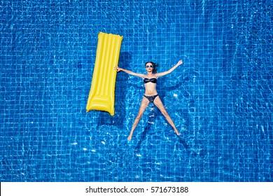 Enjoying suntan. Vacation concept. Top view of slim young woman in bikini holding yellow air mattress in the big swimming pool.
