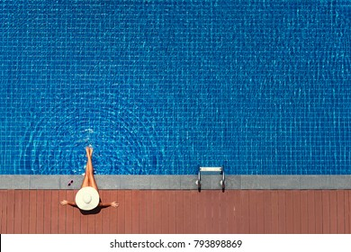 Enjoying suntan. Vacation concept. Top view of slim young woman in hat in the big swimming pool.