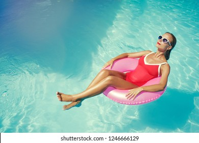 Enjoying suntan and vacation. Outdoor portrait of pretty young woman in red swimsuit with inflatable ring in swimming pool.