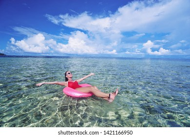 Enjoying suntan and vacation. Outdoor portrait of pretty young woman in red swimsuit on inflatable ring on tropical beach.