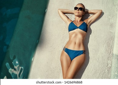 Enjoying suntan and vacation. Top view portrait of pretty young woman in blue swimsuit bikini lying near swimming pool.