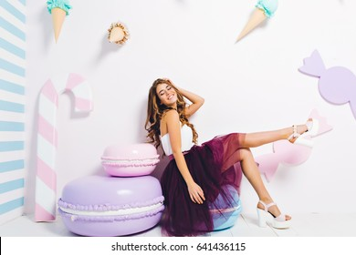 Enjoying sweet happy lifestyle of charming cute young woman with long brunette hair in purple tulle skirt sitting on big macaroon on white background. Expressing positive emotions surround big sweets