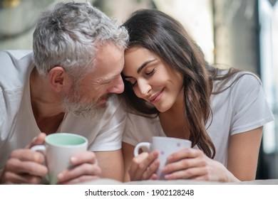 Fröhliche Zärtlichkeit. Ein schönes Paar, das morgens einen Kaffee zusammen hat