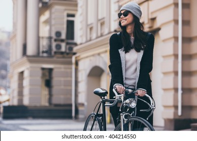 Enjoying this beautiful day. Beautiful young woman in sunglasses rolling her bicycle and looking away with smile while walking outdoors
