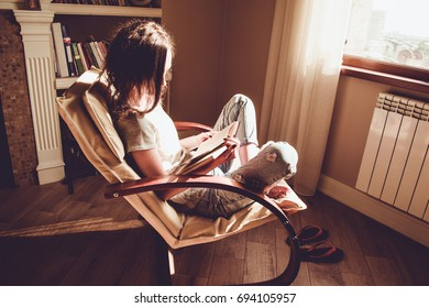 Enjoying time at home. Woman relaxing comfortable modern chair near window reading paper book. Natural light. Cozy home.Enjoy moment. Bright sunny day. Knowledge and learning concept. Bookworm student
