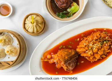 Enjoying traditional Shanghai food including dumplings, stewed meatball and mandarin fish with pine nuts