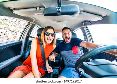 Enjoying travel in the car. Beautiful smiling young couple sitting on the front passenger seats and smiling while handsome man driving a car. Crazy happy face during selfie photo