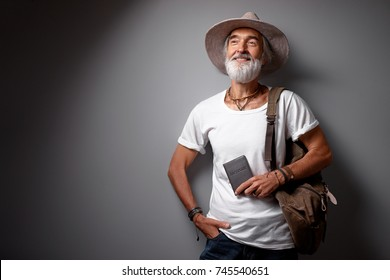 Enjoying travel. Studio portrait of handsome senior man with gray beard and hat.