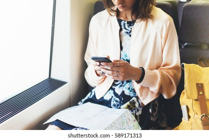 Enjoying travel. Young pretty woman traveling by train sitting near the window using smart phone and looking map. Tourist text message and plan route of railway, railroad transport concept