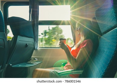 Enjoying travel. Young pretty woman traveling by the train, sitting near the window and drink coffee.