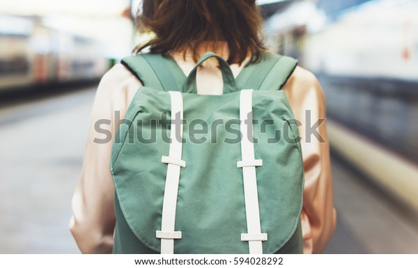Enjoying travel. Young pretty woman waiting on the station platform with backpack on background electric train. Tourist text message and plan route of railway, railroad transport concept
