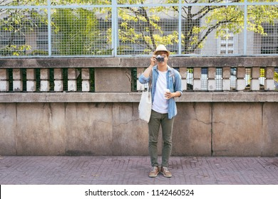 Enjoying travel. Young smiling man with backpack holding camera on asian street.