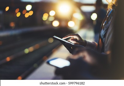 Enjoying travel. Young woman waiting on station platform on background light electric moving train using smart phone in night. Tourist text message and plan route of stop railway, railroad transport