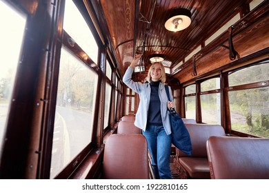 Enjoying trip. Young pretty woman traveling by old retro tramway.