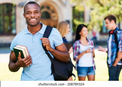 Enjoying university life. Handsome young African man holding books and smiling while standing against university with his friends chatting in the background