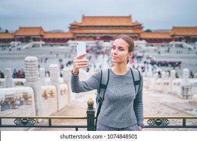 Enjoying vacation in China. Travel and technology. Young woman with smartphone taking photo at Forbidden City, Beijing.