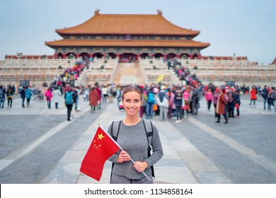 Enjoying vacation in China. Traveling young woman with national chinese in Forbidden City, Beijing.