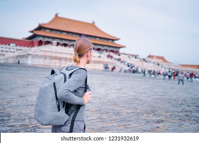 Enjoying vacation in China. Traveling young woman with rucksack in Forbidden City, Beijing.