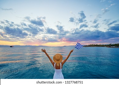 Enjoying vacation in Greece. Young traveling woman with national greek flag enjoying sunset on sea.